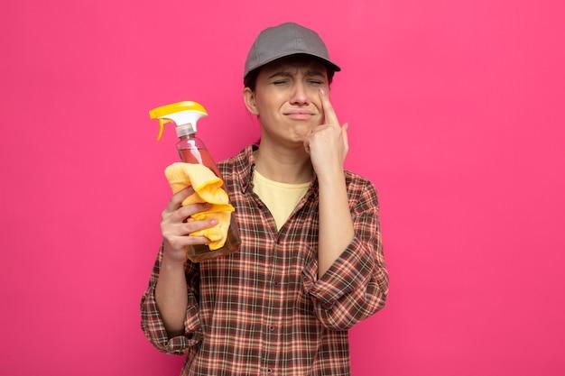Turbata giovane donna delle pulizie in abiti casual e berretto che tiene in mano uno straccio e uno spray detergente che piange forte