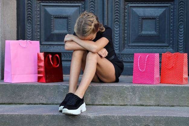 La ragazza turbata si siede con le borse colorate sui gradini del negozio
