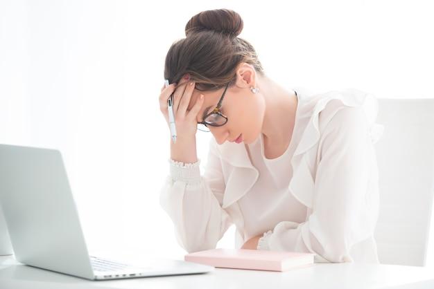 Una giovane donna sconvolta è seduta in un ufficio davanti a un laptop e si tiene la testa tra le mani.