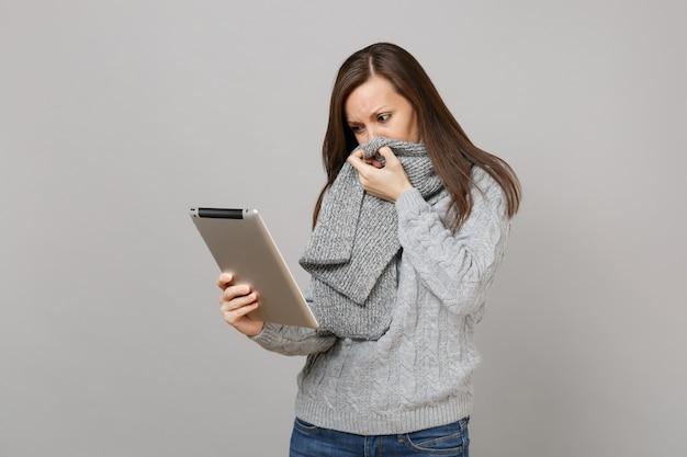 Sconvolto giovane donna in maglione che copre la bocca con sciarpa, utilizzando computer tablet pc isolato su sfondo grigio. stile di vita sano, consulenza sul trattamento online, concetto di stagione fredda. mock up copia spazio.