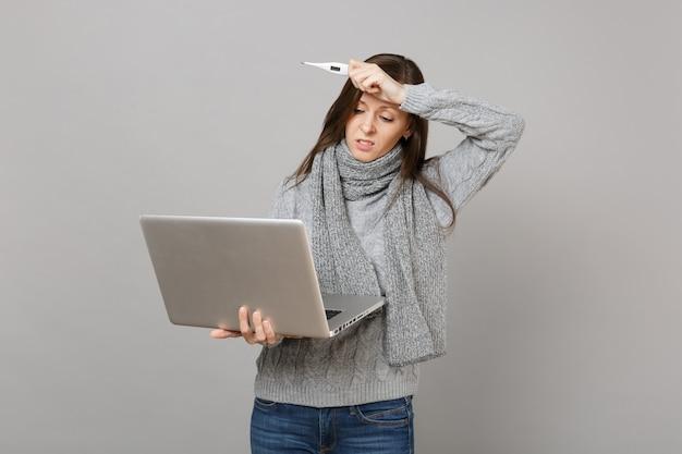 Sconvolto giovane donna in maglione, sciarpa mettere la mano sulla testa, lavorando sul computer pc portatile, tenere il termometro isolato su sfondo grigio. stile di vita sano, consulenza sul trattamento online, concetto di stagione fredda.