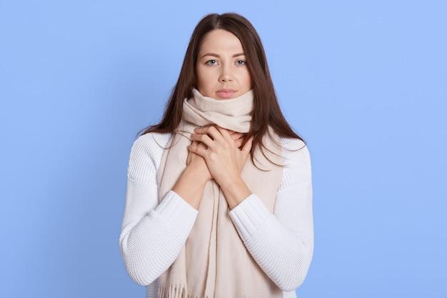 Giovane donna sconvolta in maglione bianco caldo e avvolta in una sciarpa, con mal di gola, tenendosi per mano sul collo, sente mal di gola e dolorosa deglutizione