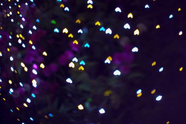 A testa in giù sfocatura a forma di cuore amore giorno di san valentino luce notturna sull'albero in giardino