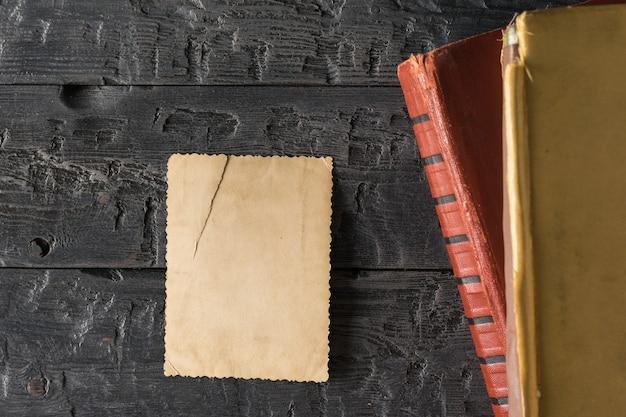 Una foto strappata capovolta con album di foto su un tavolo di legno nero. carta da lettere retrò. lay piatto.