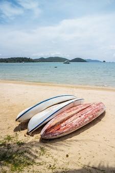 Upside down kayaks bianchi e rossi si fermano sulla spiaggia con mare e montagna con cielo blu chiaro