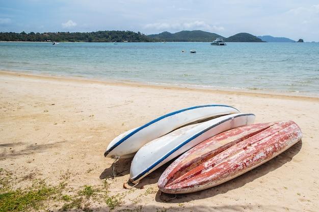 Upside down kayaks bianchi e rossi si fermano sulla spiaggia con mare e montagna