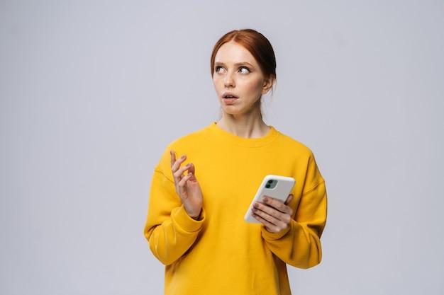 Giovane donna tesa che tiene il telefono cellulare e che guarda l'obbiettivo su sfondo bianco isolato
