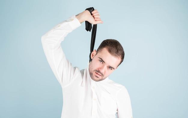 Un ritratto con lo sguardo rivolto verso l'alto di un giovane manager annoiato o stanco, stufo, che si sente a disagio mentre pende dalla cravatta