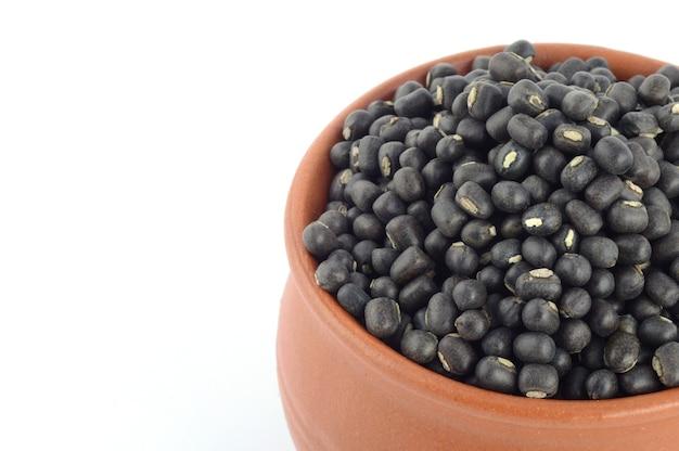 Urad dal, grammo nero, vigna mungo in vaso di terracotta su sfondo bianco