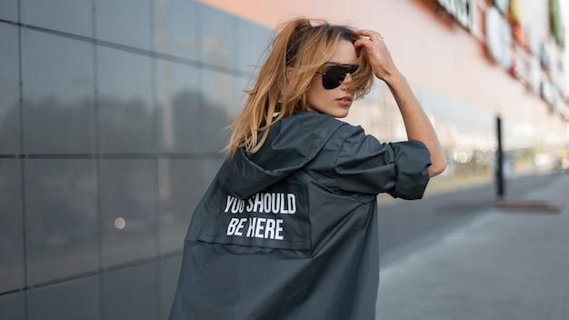 Giovane donna attraente urbana in giacca lunga alla moda in occhiali da sole alla moda in una città vicino a un moderno centro commerciale grigio. il modello alla moda della ragazza dai capelli rossi gode di una luminosa giornata di sole. stile di strada