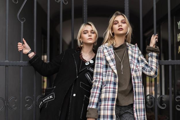 Urbane belle giovani sorelle con capelli biondi con labbra sexy in abiti vintage stanno vicino al cancello di ferro in città