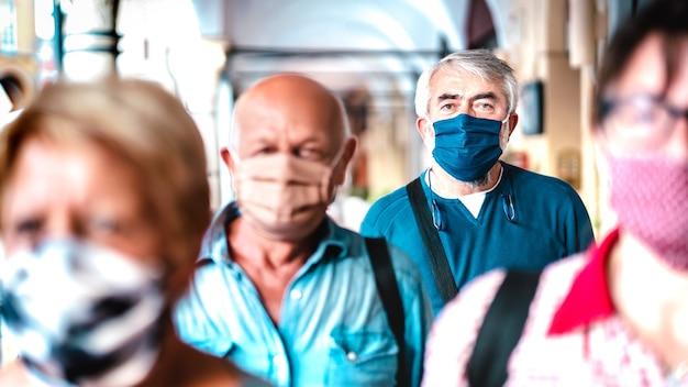 Folla urbana di cittadini adulti che camminano sulla strada della città durante la pandemia - fuoco selettivo sull'uomo con maschera blu