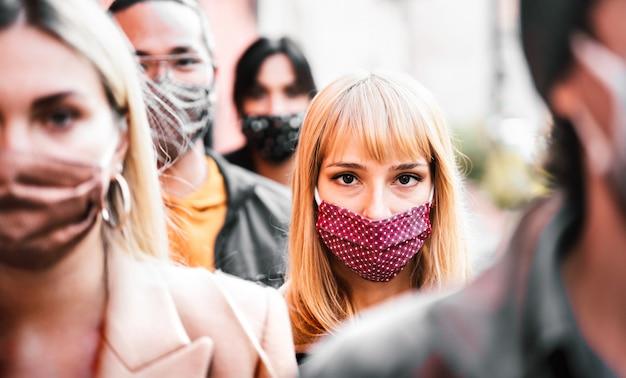Folla urbana di cittadini che camminano sulla strada cittadina coperta dalla maschera facciale - focus sulla donna bionda