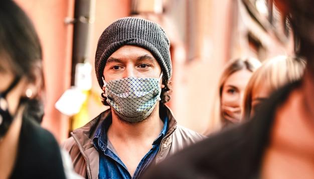 Folla urbana di cittadini che camminano sulla strada della città che indossa la maschera per il viso - fuoco selettivo sul ragazzo