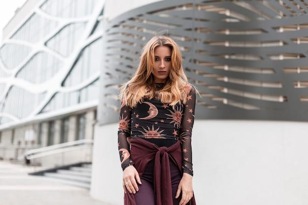 Donna abbastanza giovane europea urbana in pantaloni vintage con un mantello viola in una camicetta alla moda con un modello in posa