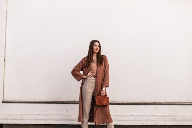 Modello di moda urbano europeo giovane donna in eleganti vestiti marroni con borsa di moda in pelle in posa vicino edificio bianco vintage sulla strada. bella ragazza in abito casual in città. signora alla moda.