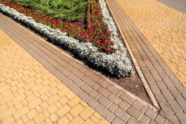 Fiori urbani nell'aiuola nella progettazione del paesaggio paesaggistica di parchi e piazze in lastre di pavimentazione urbana