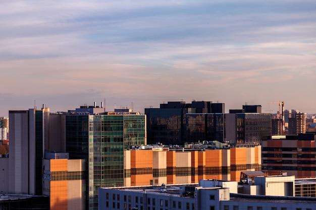Paesaggio urbano industriale la sera al tramonto. bel cielo azzurro, edifici commerciali creativi ed edifici residenziali.