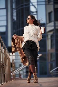 Vita di città. la giovane bella ragazza in vestiti caldi ha passeggiata in città durante il suo tempo di fine settimana