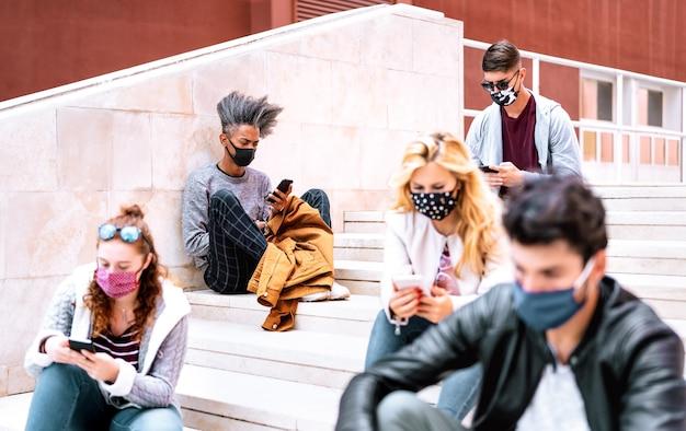 Studenti milenial urbani che utilizzano smartphone con maschera facciale sulla seconda ondata di covid