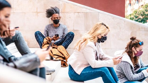I millennial urbani che utilizzano smartphone con maschera facciale sulla seconda ondata di covid