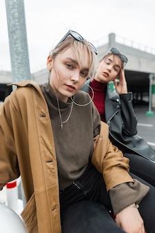 Ritratto urbano di belle giovani donne con giacca di pelle e maglione in jeans neri si siede e posa per strada