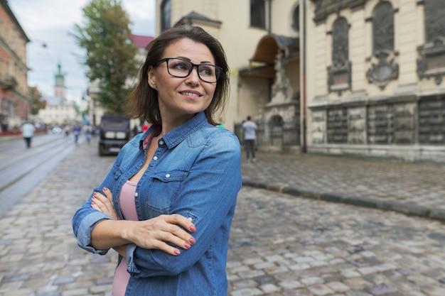 Ritratto urbano di donna matura sicura, femmina con le braccia incrociate