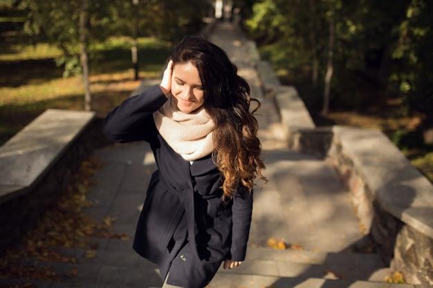 Ritratto urbano di una bella modella bruna con lunghi capelli ondulati che indossa una sciarpa lavorata a maglia rosa e un cappotto blu
