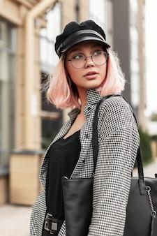 Il ritratto urbano di una giovane donna alla moda in occhiali vintage con un copricapo in una camicia alla moda con una borsa nera cammina in città