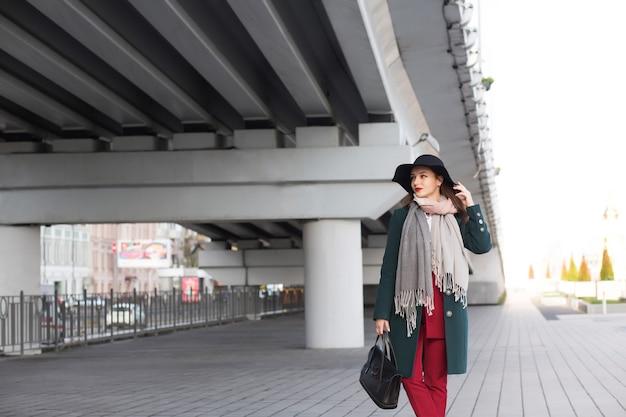 Ritratto urbano di giovane donna bruna che indossa cappotto, cappello nero e borsa. spazio per il testo