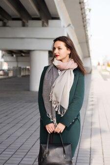 Ritratto urbano di giovane modella che indossa un cappotto caldo e tiene in mano una borsa nera. spazio per il testo