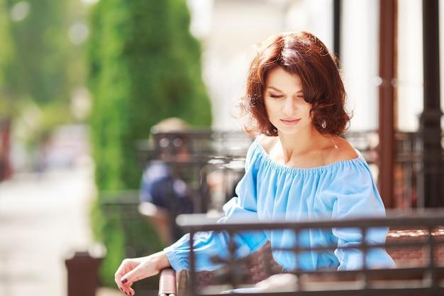 Ritratto urbano romantico di bella ragazza che indossa abito azzurro e collant bordeaux