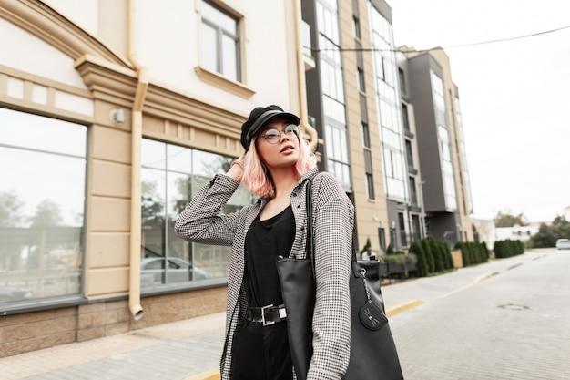 Urbana elegante bella giovane donna in occhiali vintage e un berretto in una camicia a quadri alla moda con una maglietta nera, jeans e una borsa alla moda passeggiate in città vicino all'edificio