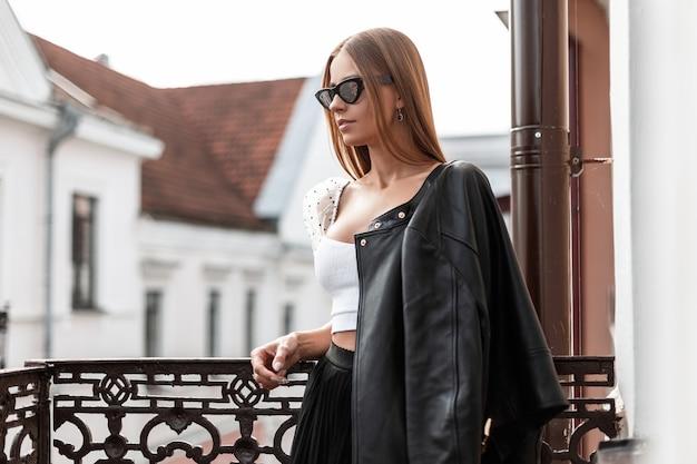 Giovane donna alla moda urbana in una giacca di pelle alla moda nera in un top alla moda in occhiali da sole si trova su un balcone in ferro vintage che si affaccia sulla strada. ragazza europea dei pantaloni a vita bassa che riposa in una giornata autunnale.