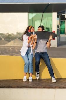 Le coppie urbane alla moda si godono l'estate nello skate park all'aperto siedono e tengono il longboard giocoso e felice insieme