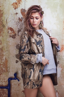 Ragazza alla moda urbana con capelli disordinati colorati in giacca mimetica