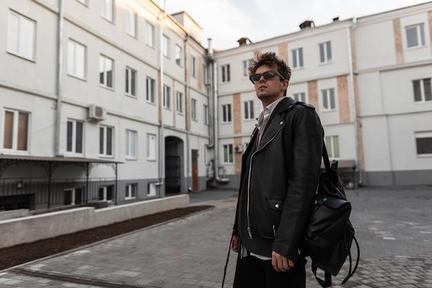Modello urbano alla moda di giovane uomo in una giacca di pelle nera alla moda oversize giovanile con acconciatura con zaino si trova vicino a un edificio moderno della città. bel ragazzo hipster in occhiali da sole all'aperto.