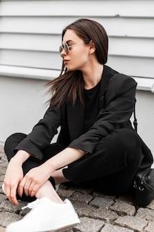 Il modello di moda urbano della giovane donna in occhiali da sole alla moda in scarpe bianche in vestiti neri alla moda con la borsa si rilassa vicino all'edificio in legno in città. la ragazza attraente in vestito casuale riposa all'aperto.
