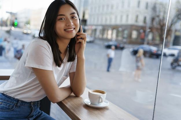 Giovane donna urbana che parla al telefono cellulare, seduto nella caffetteria vicino alla finestra e sorridente, bevendo una tazza di caffè in una calda giornata estiva