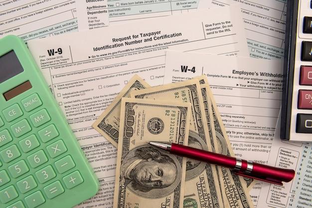 Modulo 1040 degli stati uniti con calcolatrice per banconote da un dollaro e documenti cartacei. concetto di contabilità