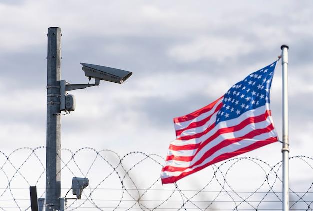 Confine usa, telecamera di sorveglianza, filo spinato e bandiera usa, immagine concettuale