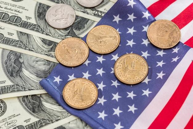 Moneta usa con banconote in dollari sulla bandiera dell'america