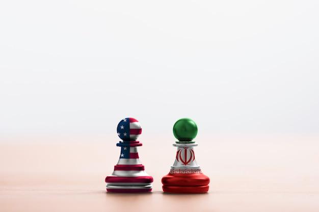 Bandiera usa e bandiera iraniana stampate su pedina degli scacchi con sfondo di luce soffusa. è il simbolo dello stato americano unito e l'iran ha conflitti nelle armi nucleari e nello stretto di hormuz.