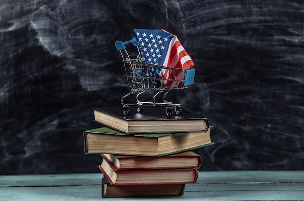 Bandiera degli stati uniti nel carrello della spesa sulla pila di libri. sfondo lavagna
