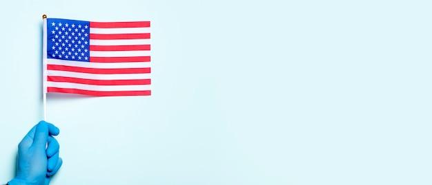 La medicina degli stati uniti e il concetto di assistenza sanitaria una mano in un guanto medico tiene la bandiera nazionale degli stati uniti