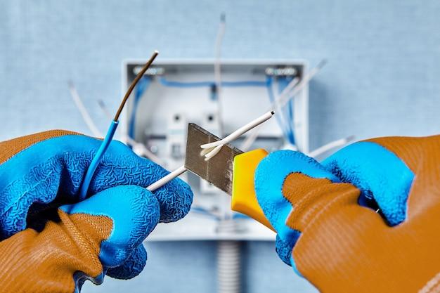Uso del coltello da costruzione durante l'installazione del quadro in un edificio residenziale, rimuovendo l'isolamento dall'estremità del filo di rame.