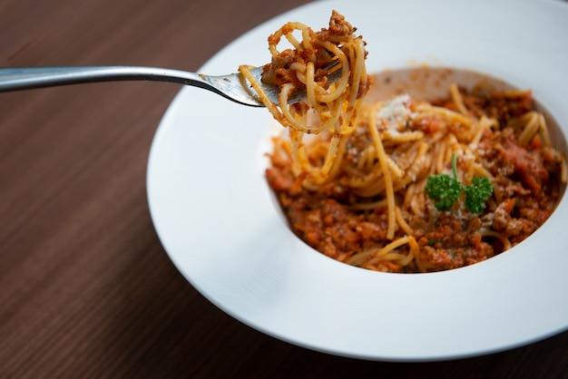 Usa una forchetta per raccogliere gli spaghetti in salsa di pomodoro, serviti su un piatto, prezzemolo in un piatto bianco, su un pavimento di legno marrone cucina italiana,