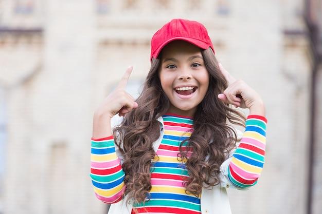 Usa il tuo cervello. il bambino felice punta le dita verso l'alto all'aperto. un bambino piccolo indossa un berretto su lunghi capelli ondulati. sorriso bambino in abbigliamento casual. accessorio di moda. stile alla moda. cura dei bambini e infanzia.