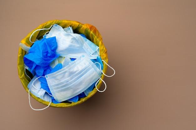 Maschere infettive usate e guanti medici nella vista dall'alto del bidone della spazzatura