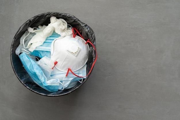 Maschere infettive usate e guanti medici nella spazzatura